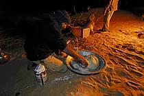 Désert du Sud Tunisien, au sud de Douz, Préparation du pain traditionnel cuit sous le sable, ref eb063723GE